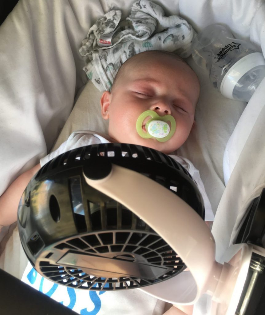 Newborn baby asleep in a pram with a fan blowing on his body to keep him cool.