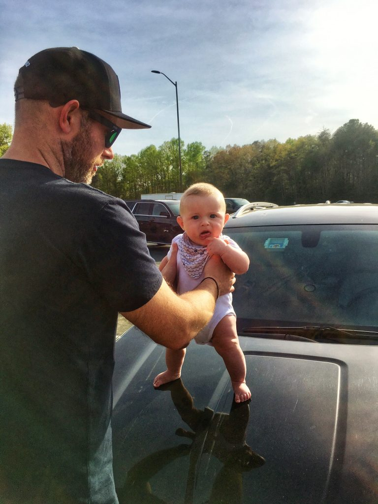 19 week old baby standing on the front of a black car in America. Being held by his dad, he is smiling as the sun shines down on him