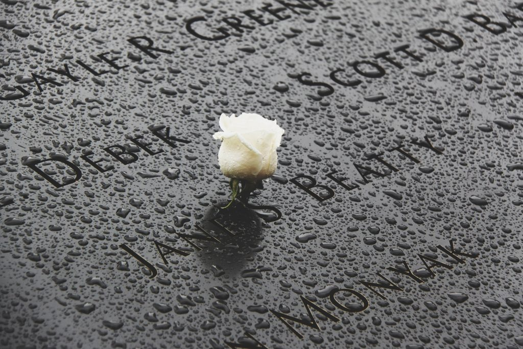A close up shot of a memorial plaque from the 9/11 memorial museum. Features several names of the deceased with a white rose centre and drops of water rolling down the grey stone.