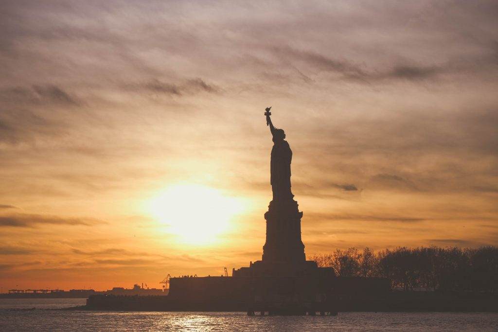 The Statue of Liberty facing out across the water, with a glowing orange sunset as the backdrop to this monument of hope.