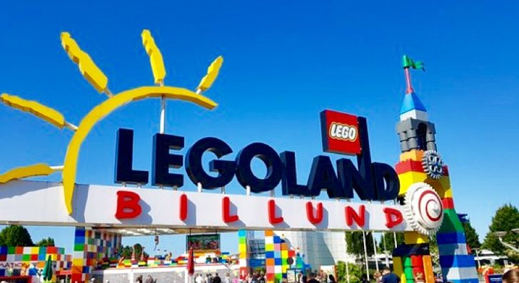 A panoramic view of the colorful Legoland, Billund entrance sign. With a clear blue sky, the sign is held up by towers made from millions of lego bircks.