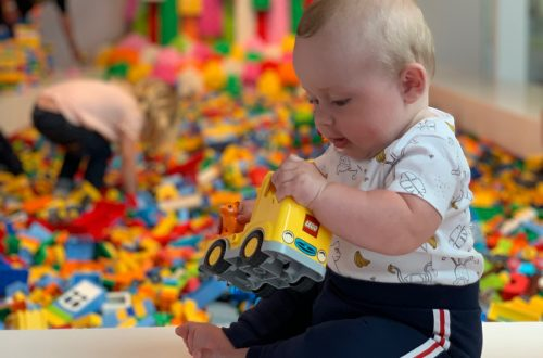 A 6 month old baby sat upright playing with LEGO at Lego House in Billund, Denmark