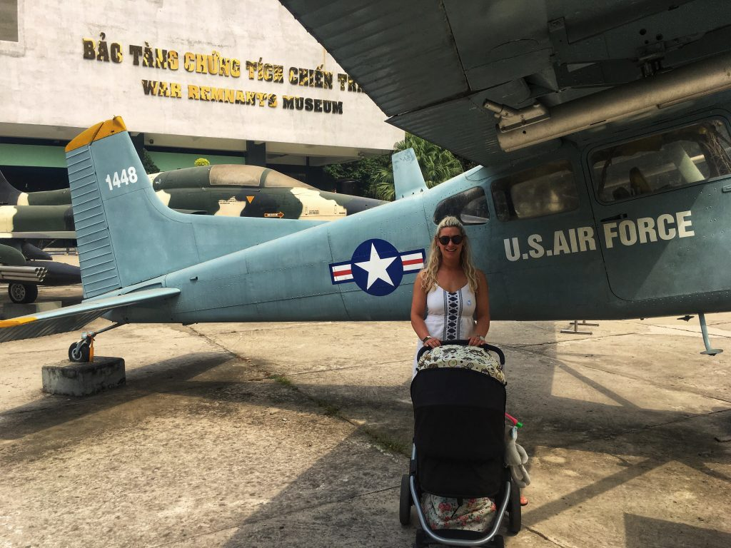 A woman with a baby in a pram stood in front of an american fighter plane. The fighter plane was left by the American army after the Vietnam war and now sits stationary in the parking lot of the War Remnants museum in Ho Chi Minh City in Vietnam