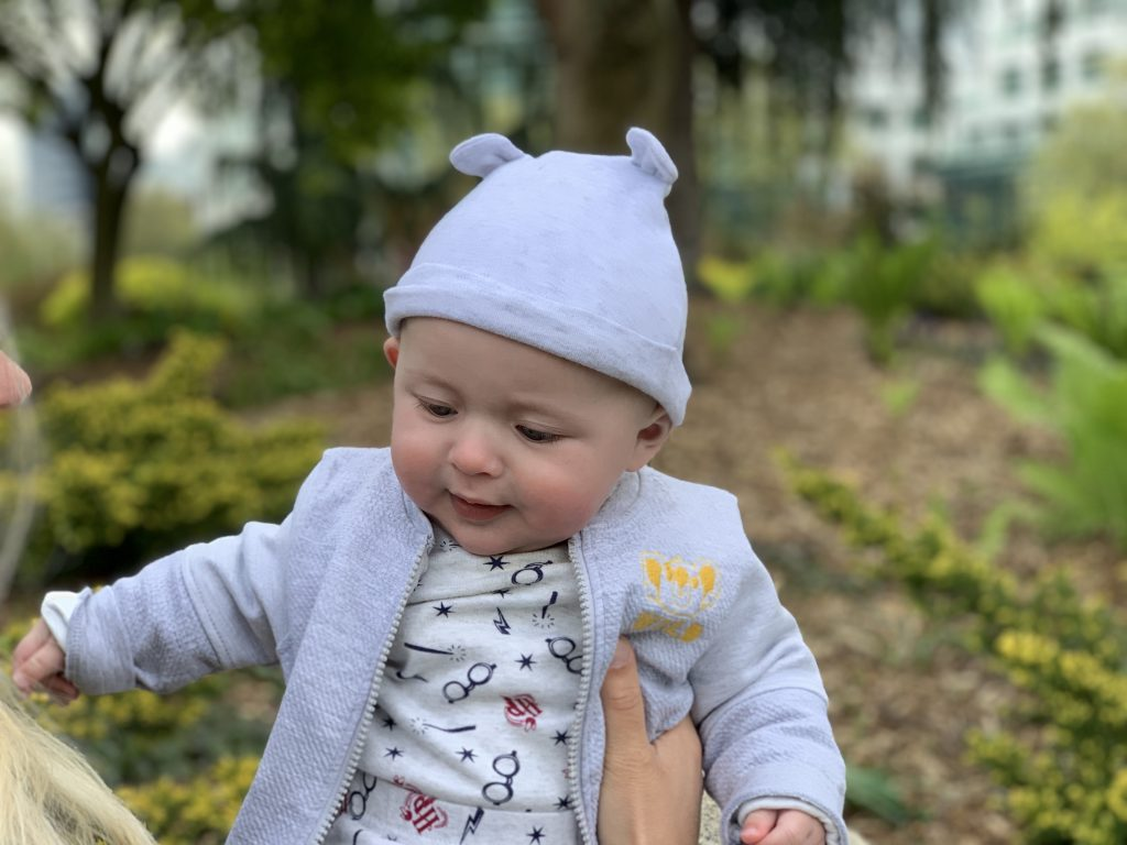 18 week old baby wearing a grey hat and Harry Potter jumper, playing with his Mother in a park in Seattle, USA