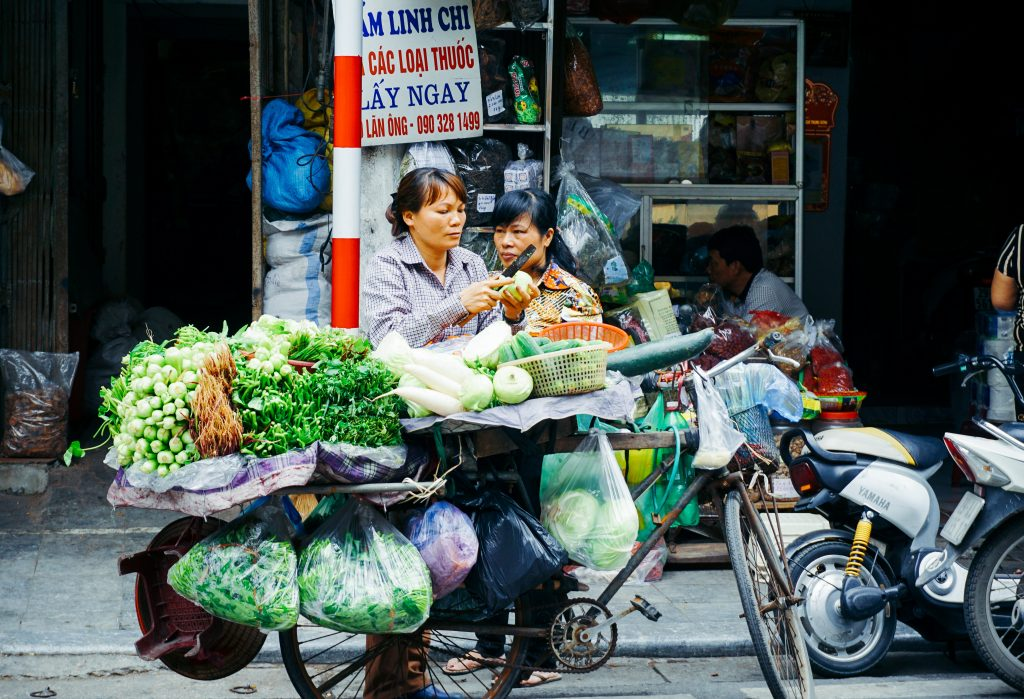 Ho Chi Minh City, Vietnam, a female street vendor is preparing food in a basket balanced on a motorbike. Standing at the side of the road, she has various fruit and vegetables in bags hanging from the back of her bike for sale.