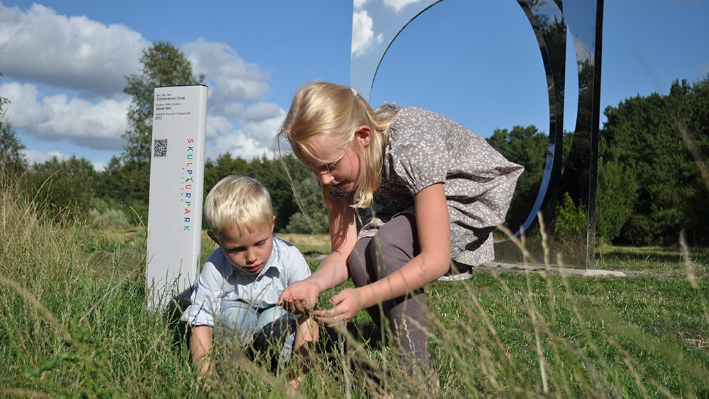A brother and sister bent down looking at a flower in a field in Skulpturpark, Billund, Denmark.