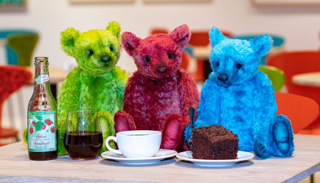 Three teddy bears, one blue, one green and one red sitting on a table in the teddy bear museum in Billund, Denmark