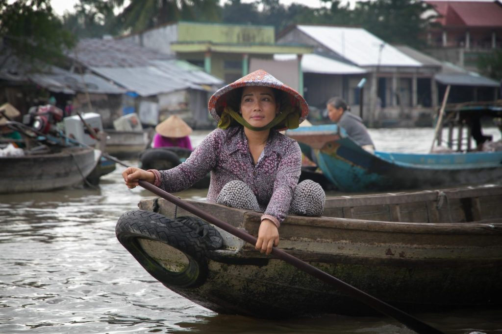 A vietnamese woman pushing a run down canoe down a busy river, mekong delta. She is by herself and wearing a traditional vietnam hat.