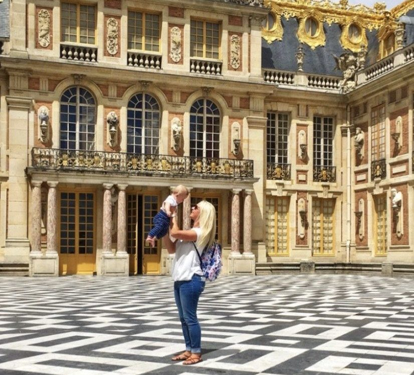 woman holding a baby in front of Versailles palace